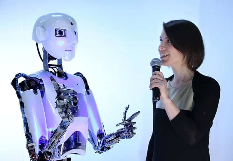 Humanoid robot talks to woman.